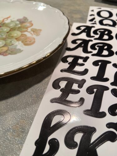 Adhesive lettering beside thrifted vintage plate