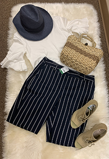 Women's white short sleeve blouse, blank pin stripe shorts, black top hat, and straw purse displayed on top of a white fur rug