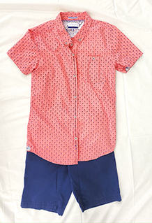 Boys outfit on display with pink short sleeve dress top with navy blue shorts.
