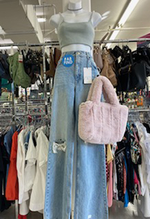 Women's blue wide leg blue jeans, crop top and pink fur purse on a manequin